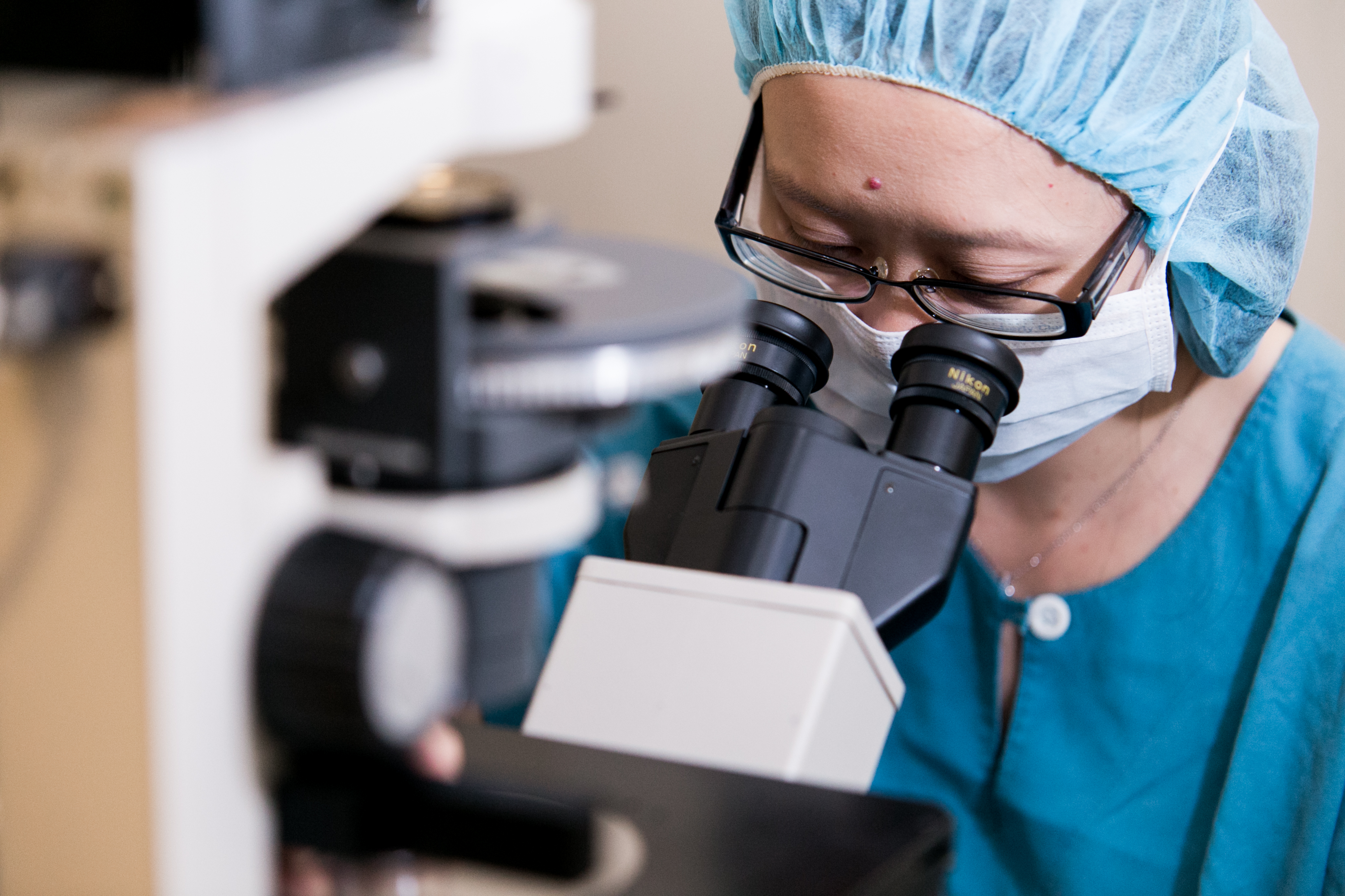 Doctor uses microscope to check for cancer cells in biopsy